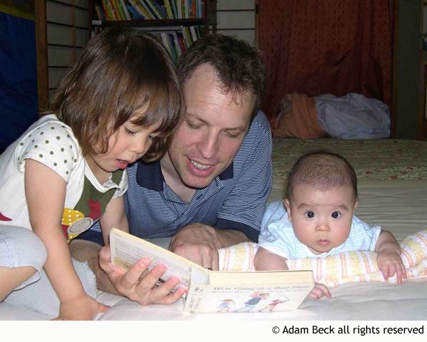 parent reading bilingual book with children