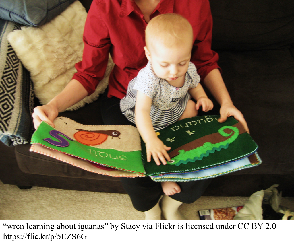 Baby reading book with parent