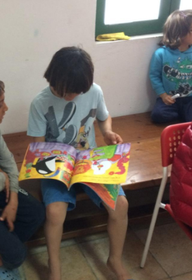 Refugee child reading a Language Lizard multicultural children's book